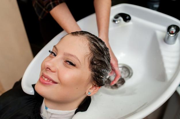 Красивая девушка мыть волосы в салоне
