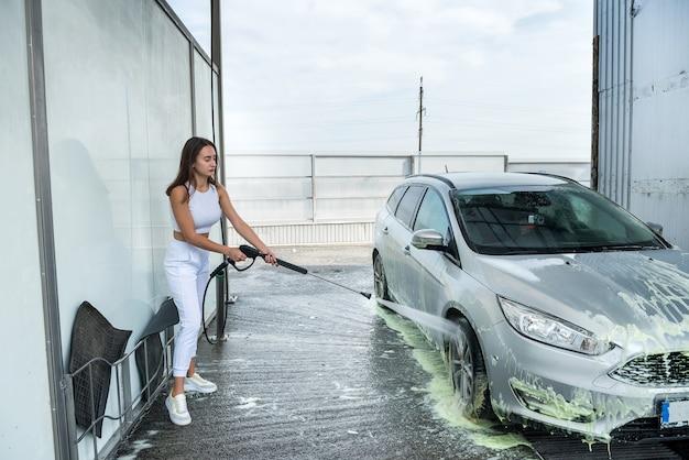 아름다운 소녀는 셀프 서비스 세차장에서 그녀의 차에서 물총으로 거품을 씻어냅니다.