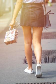 Красивая девушка в черном мини-платье и ходьба