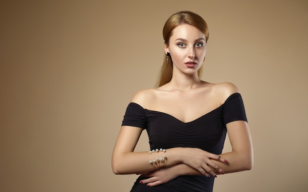Beautiful girl wearing black off shoulders dress and pearls golden bracelet on beige wall