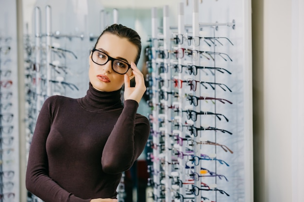 Beautiful girl wearing glasses in optician shop.