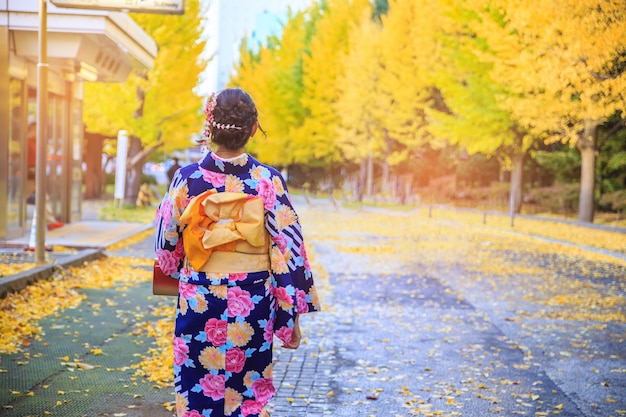 Красивая девушка в японском традиционном кимоно осенью.