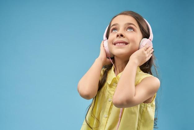 Beautiful girl wearing pink headphones, posing in studio.