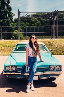 Beautiful girl wearing sunglasses stands in front of aquamarine