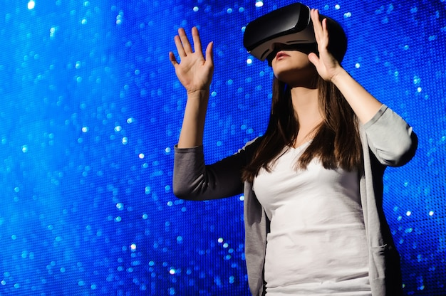 A beautiful girl wearing a virtual reality device, standing on the background of the sky.