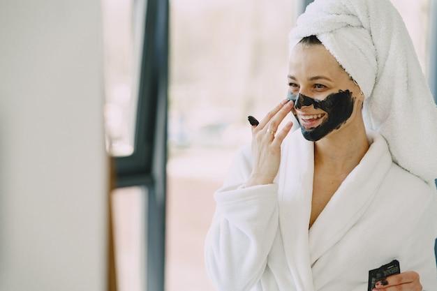 Beautiful girl in a white bathrobe at home