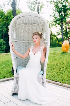 Beautiful girl in a white chair in nature. blonde in a dress with a deep neckline.