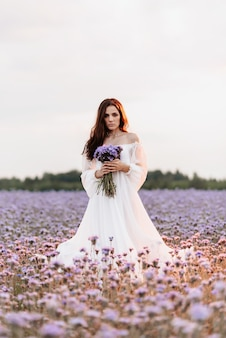 A beautiful girl in a white dress in a blooming field of provence in a romantic atmosphere with a bouquet in her hands