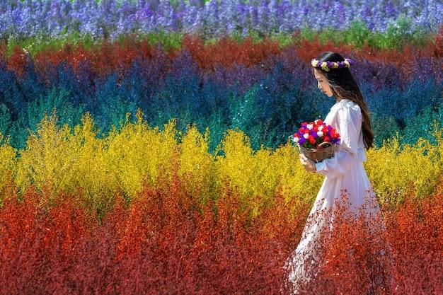 Beautiful girl in white dress sitting in cutter rainbow flowers fields, chiang mai
