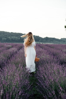 Beautiful girl in a white dress and with a basket walks on a lavender field