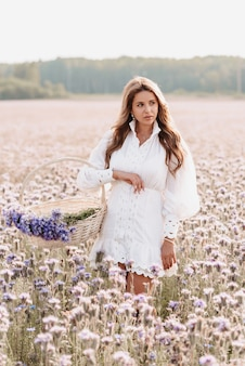Beautiful girl in a white dress with a bouquet of flowers in a basket in a field in summer