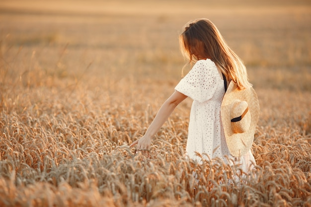 Beautiful girl in a white dress. woman in a autumn field. lady in a straw hat.