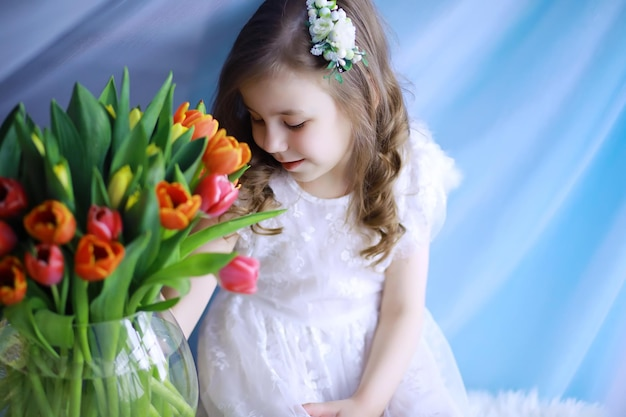 Beautiful girl in white dresses with a magnificent bouquet of the first tulips. international women's day. girl with tulips.