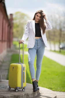 Beautiful girl in a white jacket stands with a large yellow suitcase