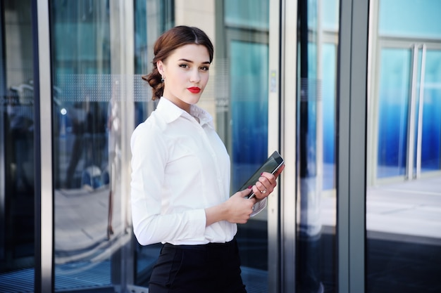 Beautiful girl in a white shirt on the background of an office building
