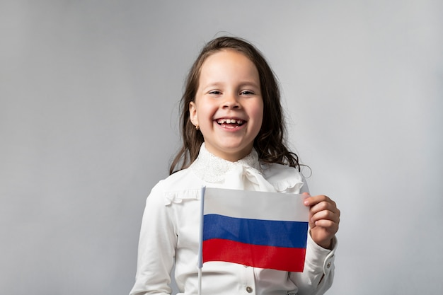 Beautiful girl in a white shirt holding the flag of the russian federation.