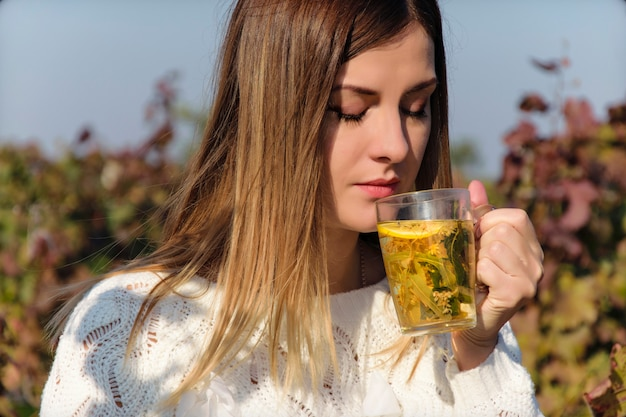 A beautiful girl in a white sweater drinks hot tea outside the house.