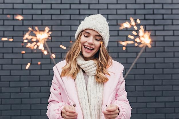 Bella ragazza in abbigliamento invernale bianco che celebra le vacanze. colpo esterno della signora romantica sorridente che tiene le luci del bengala.