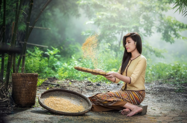 Beautiful girl winnowing rice separate between rice and rice husk, thailand countryside