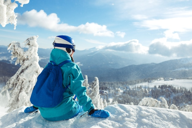 A beautiful girl in winter clothes, a blue helmet and a green jacket is having a great time in the mountains.
