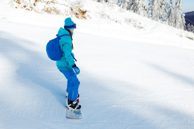 A beautiful girl in winter clothes is riding a snowboard.