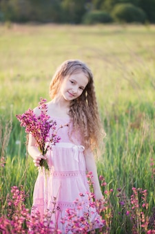 Beautiful girl wit flowers at sunset outdoor