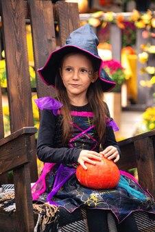 屋外の公園でカボチャと美しい少女の魔女