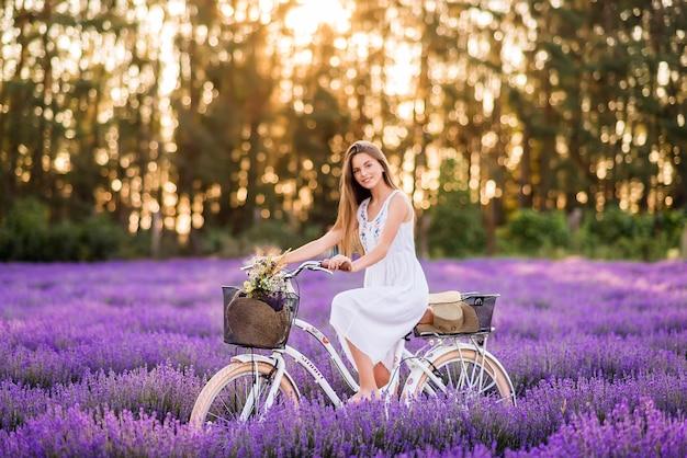 라벤더 밭에서 자전거와 함께 아름 다운 소녀. 보라색 바탕에 귀여운 소녀입니다.