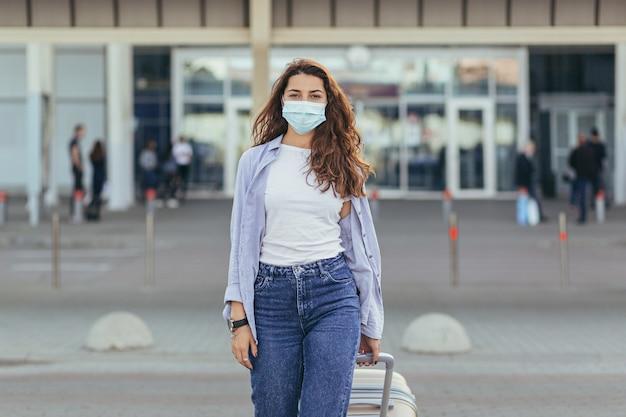 彼女の顔に保護マスクを身に着けている空港で大きなスーツケースを持つ美しい少女