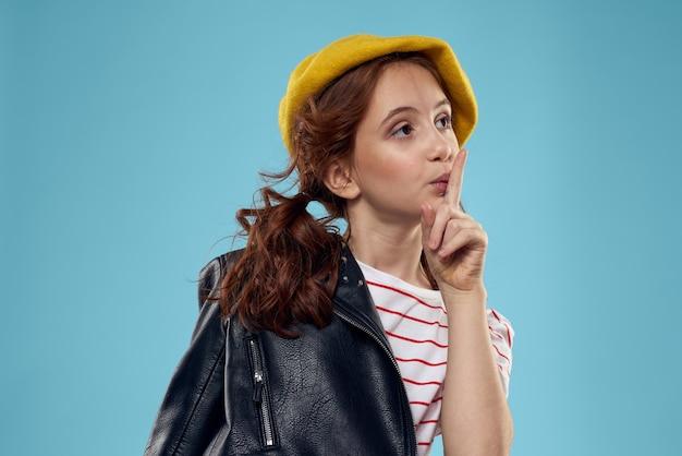 黒のジャケットと彼女の頭の赤い髪モデル青に黄色い帽子を持つ美しい少女