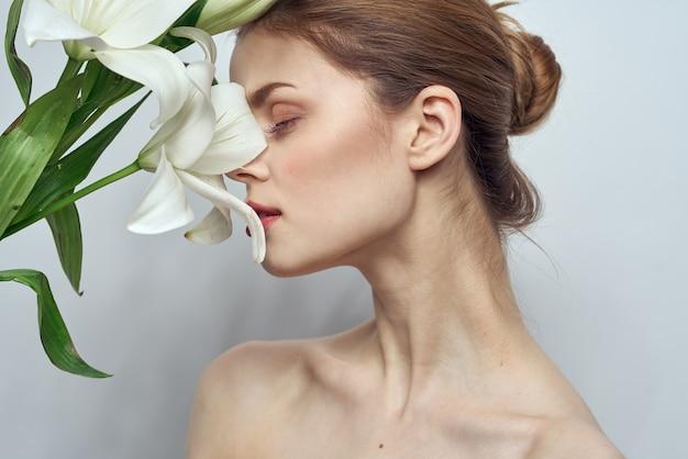 Красивая девушка с букетом белых цветов на светлом фоне голые плечи чистая кожа весна