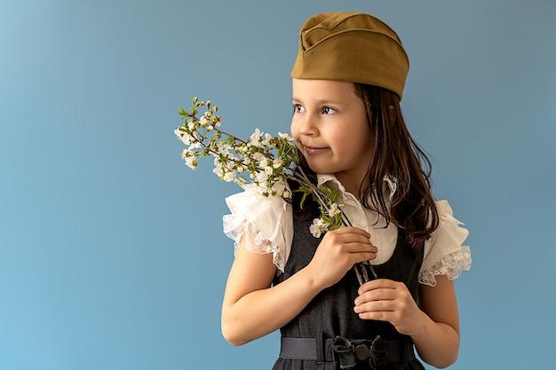 Красивая девушка с веткой цветущего дерева на тему 9 мая, день победы.