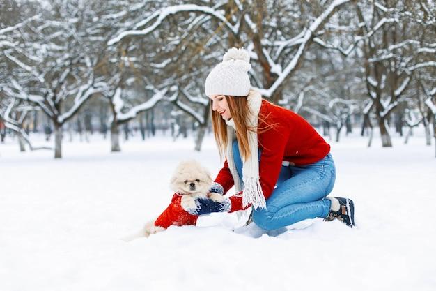 冬の公園を歩いているかわいい犬と美しい少女