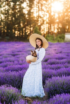 Красивая девушка с собакой в корзине в лаванде. на ней длинное платье и большая шляпа.