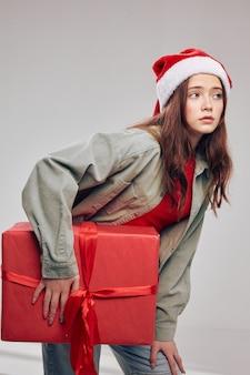 Красивая девушка с подарочной коробкой идет в сторону на сером фоне. фото высокого качества