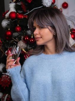 샴페인 한 잔과 함께 아름다운 소녀가 크리스마스 트리에서 새해와 크리스마스를 만납니다.