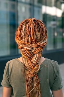 Красивая девушка с длинной косой из красных дредов. девушка стоит спиной к камере. крупный план.