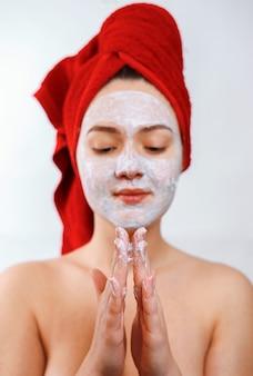 Красивая девушка с красным полотенцем на голове наносит скраб на лицо