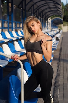 Красивая девушка со спортивным телом позирует на стадионе