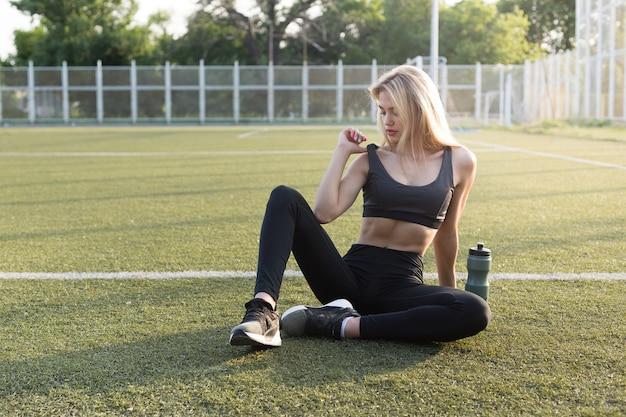 スタジアムの芝生の上にスポーティな体の美少女が座る