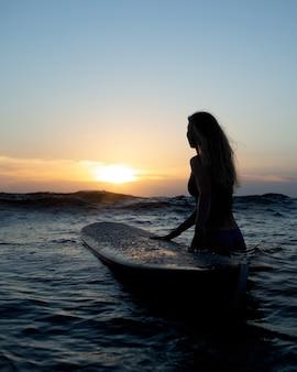 Красивая девушка с доской для серфинга на закате