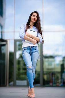 Красивая девушка с планшетом на улице.