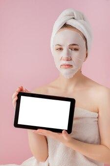 핑크 공간에 복사 공간이 그들의 손에 티슈 마스크와 태블릿 아름다운 소녀