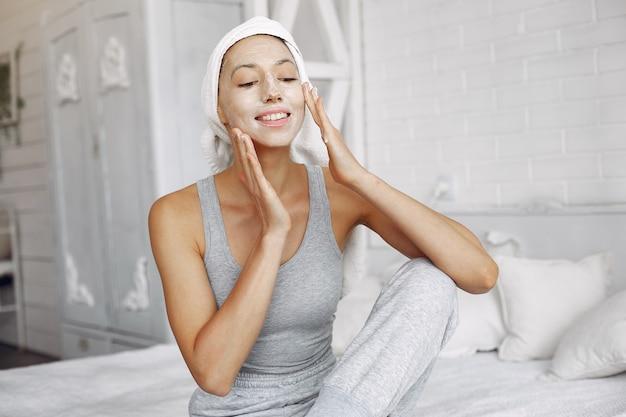 Красивая девушка с полотенцем, используя косметический продукт