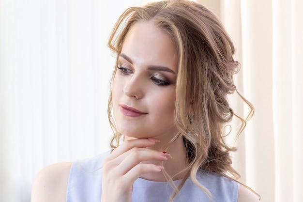 結婚式のヘアスタイルを持つ美しい少女は、鏡、若い女の子の肖像画で自分自身を見ます。美しいメイク。美容サロン