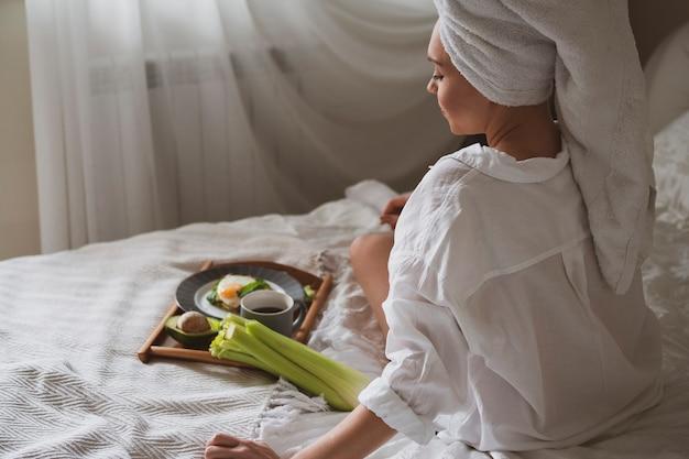 Красивая девушка с белым полотенцем на голове сидит в постели и собирается завтракать