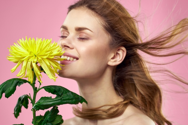 ピンクの壁に黄色い花を持つ美しい少女