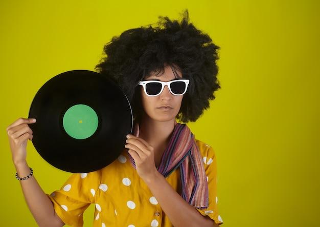 アフロの巻き毛のヘアスタイルと黄色の壁にlpレコードを保持している白い眼鏡の美しい少女