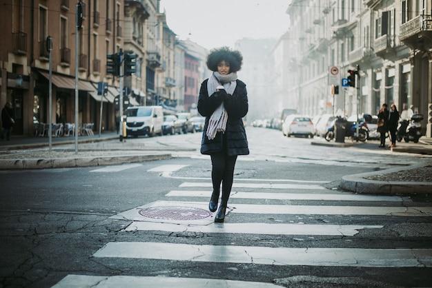 거리에 걷는 아프로 머리를 가진 아름 다운 소녀 프리미엄 사진