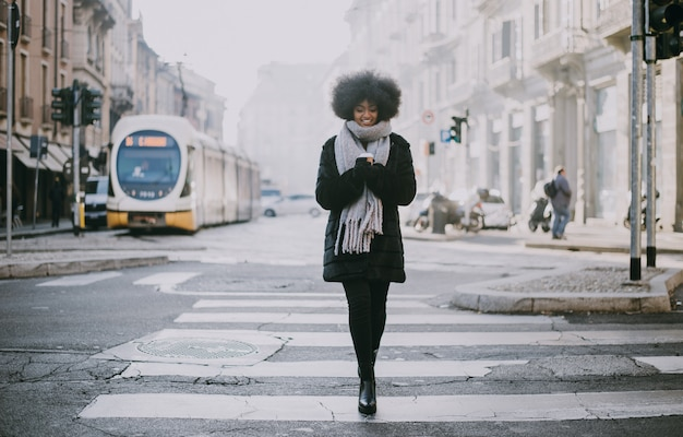 거리에 걷는 아프로 머리를 가진 아름 다운 소녀